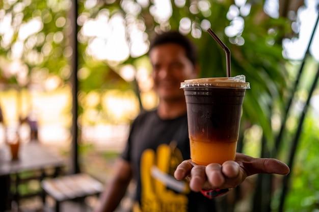 手にプラスチックガラスのオレンジジュースとアイスコーヒーミックス