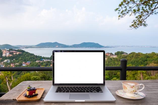 山の街の景色に木製のテーブルの上のイチゴケーキとコーヒーカップとラップトップコンピューター