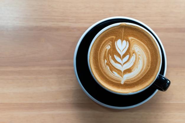 木製のテーブル、上面に黒いカップでラテアートコーヒー。