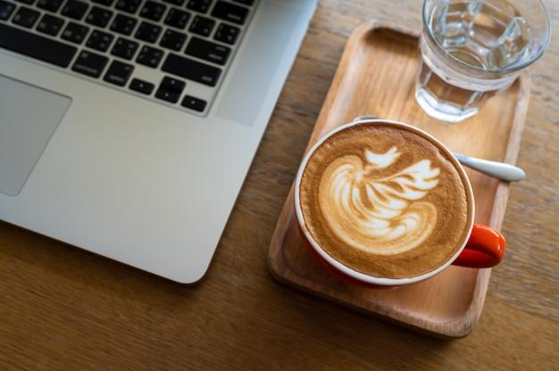 ラポップコンピューターと木製のテーブルの上のラテアートコーヒーカップ