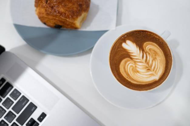 Закройте латте арт кофе кубок с клавиатурой портативного компьютера