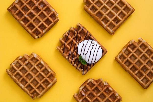 チョコレートソース、アイスクリーム、黄色のテーブルにミントのワッフルパターン
