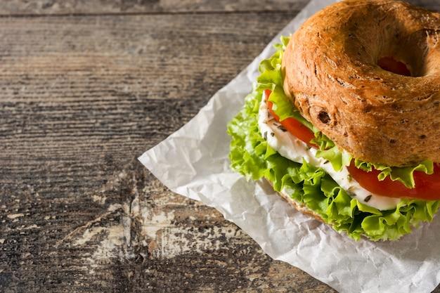 木製テーブルの上のトマトレタスとモッツァレラチーズの野菜ベーグルサンドイッチ