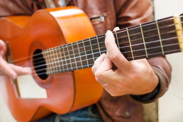 廃墟の都会的なスタイルのギターを持つ男