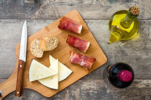 Испанская ветчина серрано, сырное вино и оливковое масло на деревенском деревянном столе