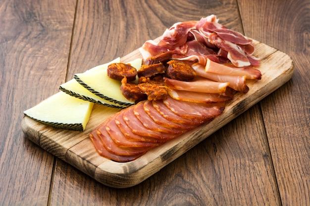 スペインのコールドカット。チーズ、ソーセージ、ハムの木製テーブル