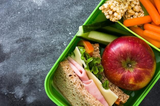 黒い石にサンドイッチ、野菜、果物が入ったヘルシースクールランチボックス