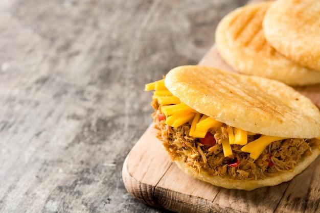 Арепа с измельченной говядиной и сыром на деревянном столе типичная венесуэльская еда