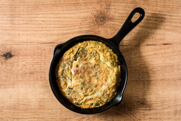 卵と野菜の鉄鍋、木製テーブルトップビューで作られたフリッタータ