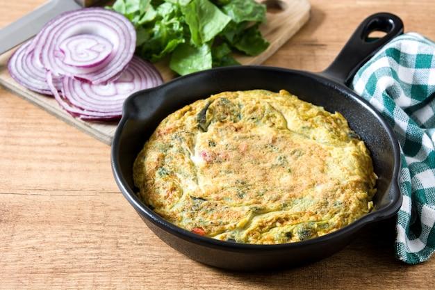 卵と野菜の鉄鍋、木製のテーブルで作られたフリッタータ
