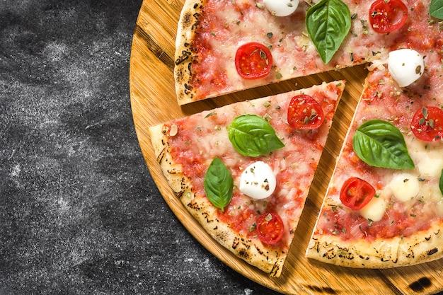 トマト、チーズ、バジルの黒い石の上でイタリアのピザのスライス