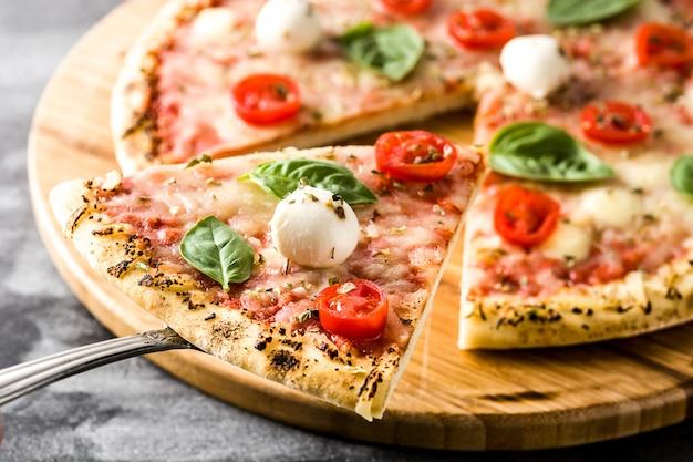トマト、チーズ、バジルの黒い石の上でイタリアのピザのスライスをクローズアップ