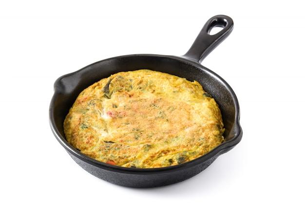 卵と野菜を白で隔離され、鉄鍋で作ったフリッタータ