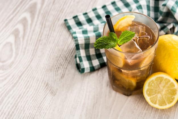 ガラスのレモンと白い木製のテーブルの上の氷とアイスティードリンク