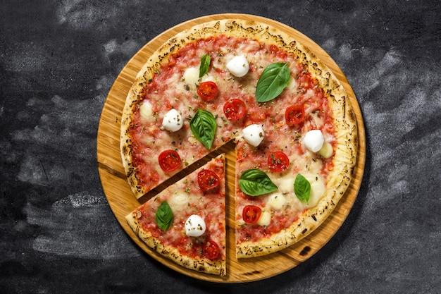 トマト、チーズ、バジルの黒い石の上でイタリアのピザのスライストップビュー