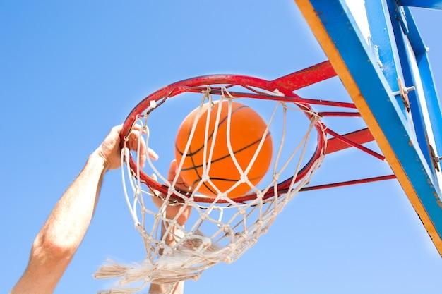 男は通りでバスケットボールをプレー