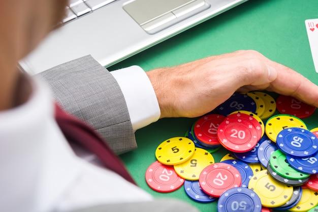 Молодой человек собирает фишки для покера