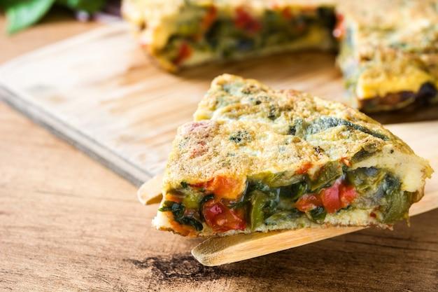 フリッタータは卵と野菜の木製のテーブルで作られました。