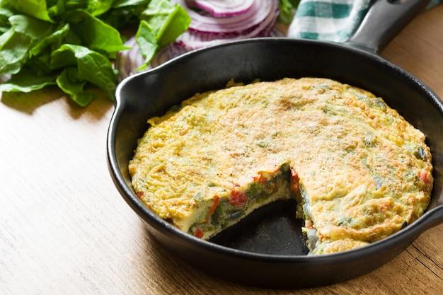 フリッタータは、木製のテーブルの上の鉄鍋に卵と野菜で作られました。