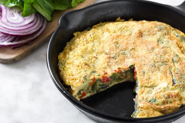 白い大理石の鉄鍋に卵と野菜で作られたフリッタータ