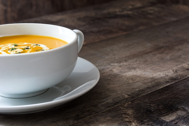 木製のテーブルコピースペースに白いボウルにカボチャのスープ