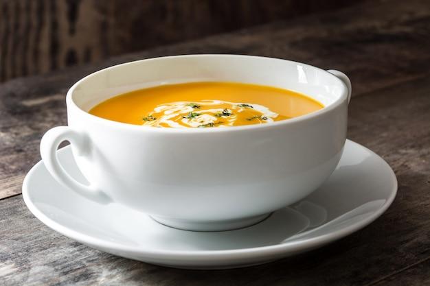 木製のテーブルの上の白いボウルのカボチャのスープ