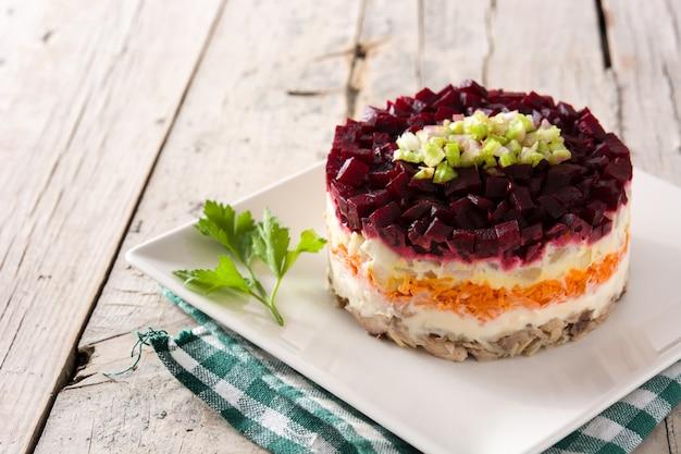 Традиционный русский салат из сельди на деревянный стол