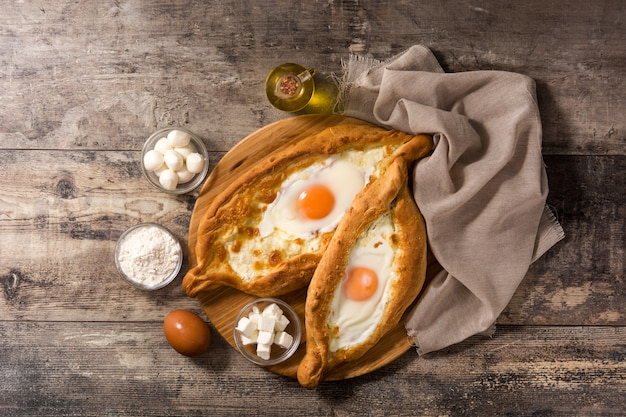伝統的なアジャリアングルジアハチャプリとチーズと卵の木製のテーブル