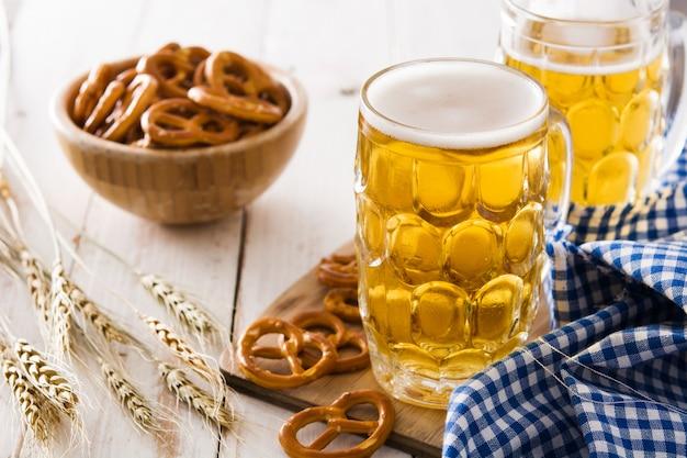 オクトーバーフェストビールと白い木製のテーブルのプレッツェル