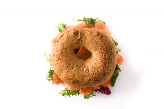 Бублик сэндвич с сыром, копченым лососем и овощами, изолированные на белом, вид сверху