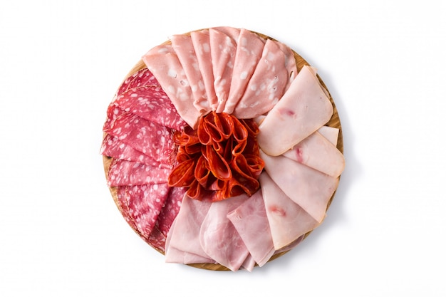 白い背景に分離されたまな板の上の冷たい肉。ハム、サラミ、ソーセージモルタデッラ、トルコ