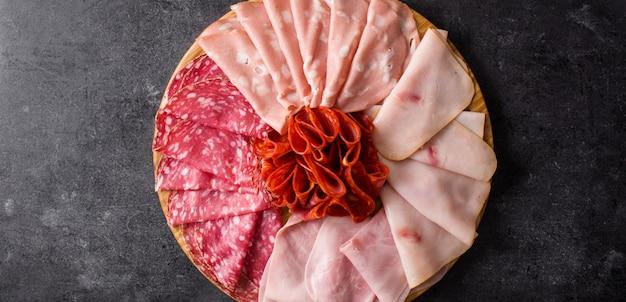黒い背景のパノラマビューにハム、サラミ、ソーセージモルタデッラ、トルコのまな板の上の冷たい肉