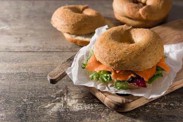クリームチーズ、スモークサーモンと木製のテーブルの上の野菜のベーグルサンドイッチ