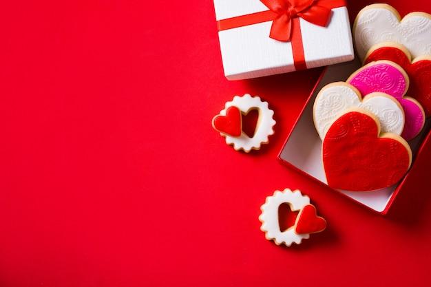 Печенье в форме сердца на день святого валентина в подарочной коробке на красном, копия пространства