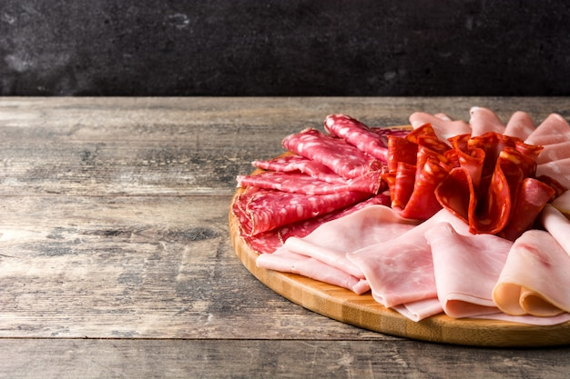 ハム、サラミ、ソーセージモルタデッラ、七面鳥、コピースペースを含む木製のテーブルにまな板の上の冷たい肉