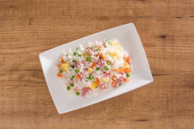 Китайский жареный рис с овощами и омлетом на деревянном столе