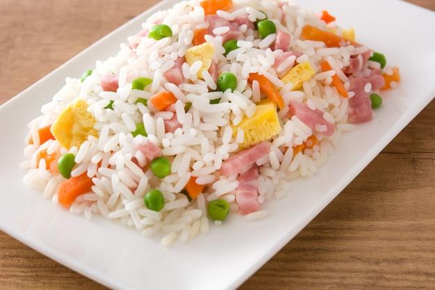 Китайский жареный рис с овощами и омлет на деревянном столе крупным планом