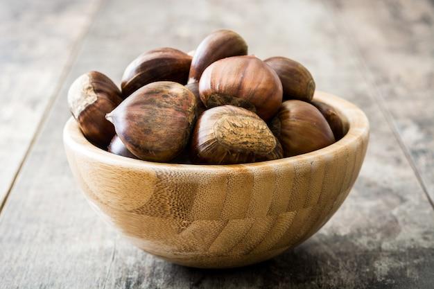 Каштаны в миске на деревянном