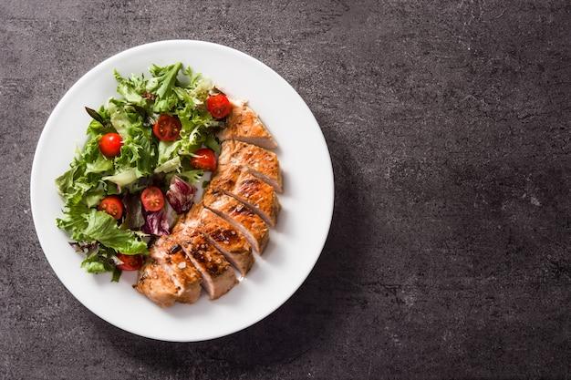 黒のトップビューコピースペースに皿に野菜と鶏の胸肉グリル