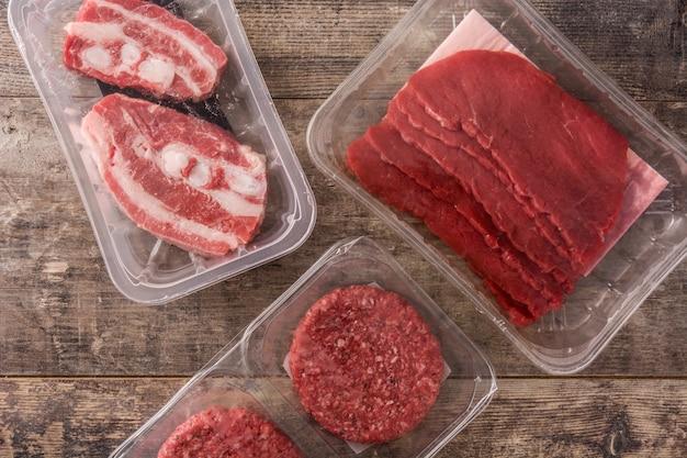 Различные виды мяса, упакованные в пластик на деревянный стол. вид сверху