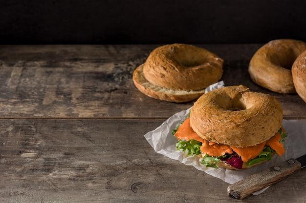 クリームチーズ、スモークサーモン、木製のテーブルに野菜のベーグルサンドイッチコピースペース