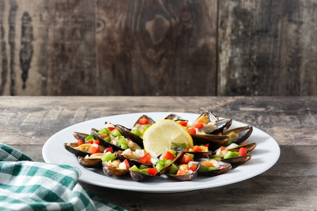 ムール貝の蒸しピーマンと玉ねぎの木製テーブル