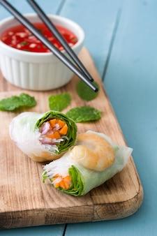 Вьетнамские роллы с овощами, рисовой лапшой и креветками на синей деревянной поверхности