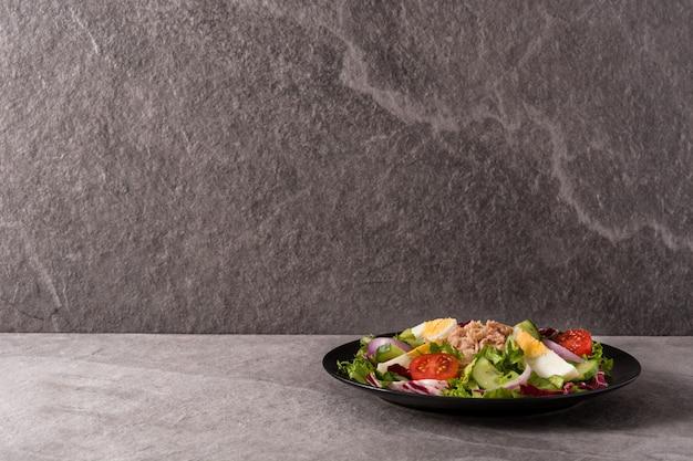 Салат с тунцом, яйцом и овощами на черной тарелке и серой поверхности