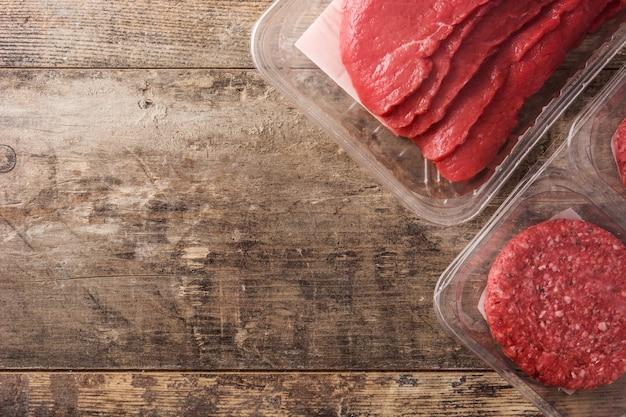 Различные виды мяса, упакованные в пластик на деревянный стол