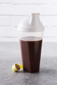 Шоколадный протеиновый коктейль на сером камне.