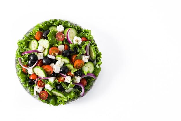 Свежий греческий салат в тарелке с черными оливками, помидорами, сыром фета, огурцом и луком на белом