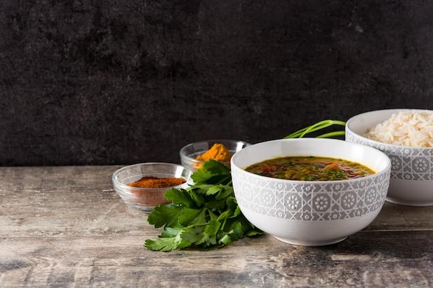Индийский суп из чечевицы дал (дхал) в миску и рис басмати на деревянный стол. копировать пространство