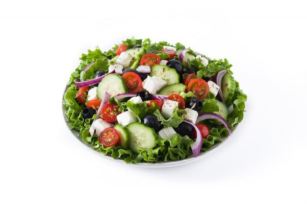Свежий греческий салат в тарелку с черными оливками, помидор, сыр фета, огурец на белом.