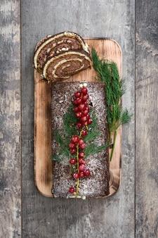 Рождественский пирог из шоколадного юла с красной смородиной на деревянном фоне